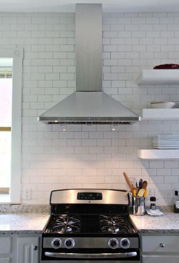 A remodeled kitchen with wall mounted chimney hood