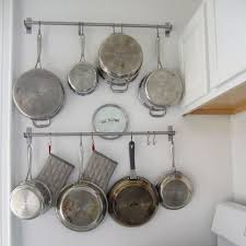 hang pots and pans on hooks to use all available space in a small kitchen